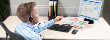 Picture of a man working at his desk wearing a telephone headset.