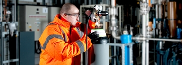 Man in high vis jacket and safety glasses inspecting cylinder valve in a plant environment.