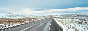 Empty road inthe countryside of Iceland with a little snow on the side